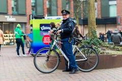 DELFTFAJANS Nederländerna - JANUARI 18, 2014: Vänlig holländsk polis på granskningar för en cykel på en upptagen fyrkant i delftf royaltyfri foto