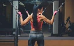 Delgada, la muchacha del culturista, hace los ejercicios que se colocan delante del espejo en el gimnasio Imágenes de archivo libres de regalías