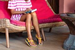 Delgado paga da mulher bonita que senta-se em um sof? cor-de-rosa e que mant?m um livro Interior no estilo ?tnico Fim acima fotos de stock
