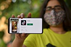 Free Delhi, India, 2020. Girl Wearing Mask Showing TikTok Mobile App On A Smartphone Depicting Logo Of The Popular Fast Growing Social Stock Photo - 185889180