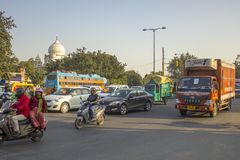 Indian city traffic of various motorcycles and vehicles on the background of green trees and the dome of stock photo
