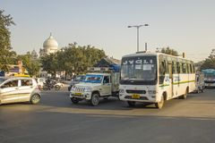 Indian white bus, moto and car traffic on city streets. Delhi India - 09.02.2019 Indian white bus, moto and car traffic on city streets royalty free stock photography