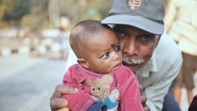 Delhi, India - November 28, 2018: Portraits of a beggar and a dirty child and her grandfather on the streets of Delhi.