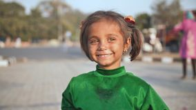 Delhi, India - November 28, 2018: Portraits of a poor child of a girl working and begging on the streets of Delhi.