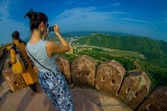 DELHI, INDIA - SEPTEMBER 25 2017: Een toeristenvrouw die beelden van het mooie landschap van Amber Fort met groen nemen Stock Foto