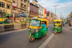 DELHI, INDIA - SEPTEMBER 25 2017: Niet geïdentificeerde mensen binnen van groene motrocycles in de weg in Paharganj, Delhi Stock Foto's