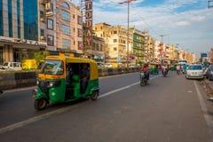 DELHI, INDIA - SEPTEMBER 25 2017: Niet geïdentificeerde mensen binnen van groene motrocycles in de weg in Paharganj, Delhi Stock Foto