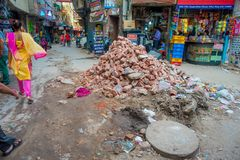 Delhi, India - September 25, 2017: Unidentified people walking in the streets near to a food stores with a pile of rocks Royalty Free Stock Photography