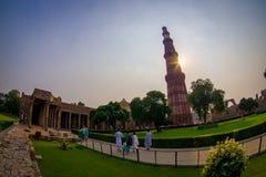 DELHI, INDIA - 25 SETTEMBRE 2017: Gente non identificata che cammina vicino di Qutub Minar in un tramonto, l'indipendente più alt Immagini Stock