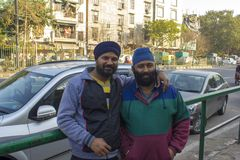 Two indian bearded men in blue turbans hugging against the background of the city road royalty free stock photography