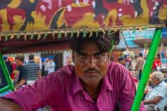 DELHI INDIA, WRZESIEŃ, - 25 2017: Portret mężczyzna jest ubranym purpurową koszulkę wśrodku riksza czekania dla ludzi, wewnątrz Obrazy Stock