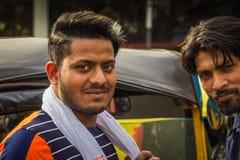 Delhi Indien - mars 19, 2019: Indiskt tempo för person som drar en skottkärra för automatiskrickshaw tre, man för taxichaufför royaltyfria foton
