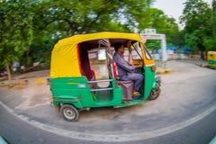DELHI, INDIEN - 19. SEPTEMBER 2017: Autorickshaw gelb und grün in der Straße, paharganj es gibt viel touristischer Aufenthalt Stockfotografie