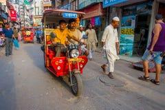 DELHI, INDIEN - 25. SEPTEMBER 2017: Nicht identifizierte Leute, die in eine schmutzige Straße in Paharganj, Delhi mit rote Riksch Lizenzfreie Stockfotografie