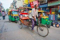 DELHI INDIEN - SEPTEMBER 25 2017: Oidentifierad man som cyklar bredvid Rickshaws som parkeras i gatorna och en automatisk Arkivbilder