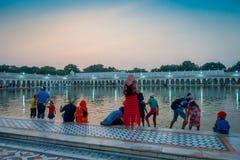 DELHI INDIEN - SEPTEMBER 19, 2017: Oidentifierat folk som simmar och tvättar deras huvud som lyckliga i dammet i Arkivbild