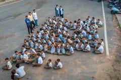 Delhi, la India - 16 de septiembre de 2017: La opinión aérea el grupo no identificado de niños que llevan deporte viste, sentándo Imagenes de archivo