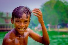 Delhi, la India - 16 de septiembre de 2017: Retrato de ascendente del muchacho indio sonriente no identificado, tocando su cabeza Fotos de archivo