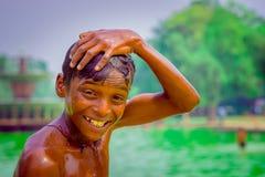 Delhi, la India - 16 de septiembre de 2017: Retrato de ascendente del muchacho indio sonriente no identificado, tocando su cabeza Imagen de archivo