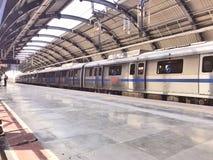 Delhi-Metrozug an einer weniger gedrängten Metrostation in Neu-Delhi in der Mittagszeit stockfotos