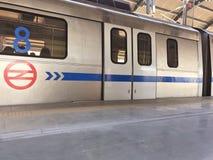 Delhi-Metrozug an einer weniger gedrängten Metrostation in Neu-Delhi in der Mittagszeit lizenzfreies stockfoto