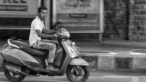DELI, ÍNDIA - 17 DE FEVEREIRO DE 2019: Montada em um movimento borrado scooty do ativa fotografia de stock
