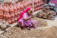 DELI, ÍNDIA - 22 DE OUTUBRO DE 2016: Mulher adulta que esmaga partes de argila no centro de Deli, Indi imagens de stock royalty free
