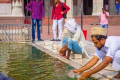 Deli, Índia - 27 de setembro de 2017: Feche acima de homem não identificado que lava suas mãos usando a água do pong no Foto de Stock