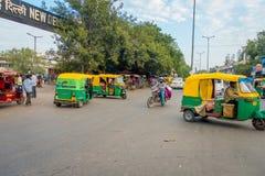 DELI, ÍNDIA - 25 DE SETEMBRO DE 2017: Povos não identificados com riquexós verdes e auto-riquexós que conduzem no Imagens de Stock