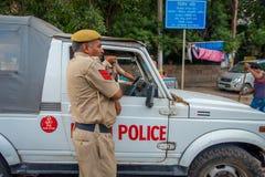 DELI, ÍNDIA - 25 DE SETEMBRO DE 2017: Um polícia de tráfego que controla o tráfego na área de Chandi Chowk da cidade tráfego Imagem de Stock