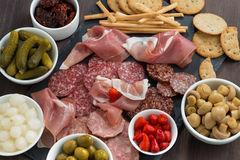 deli meat snacks, sausages and pickles on a blackboard, close-up Stock Photos