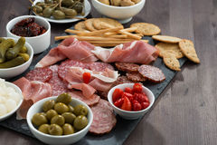 deli meat snacks, sausages and pickles on a dark wooden table Stock Photo
