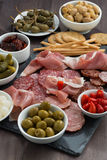 Deli meat snacks, sausages and pickles on a dark wooden table Royalty Free Stock Images