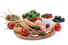 Deli meats, pickles and olives on a wooden board, isolated Royalty Free Stock Photo