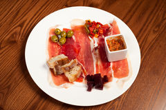Deli meats on a white plate. Delicatessen items on a white plate such as Serrano ham, home cured Bresaola, chorizo salsa, pickles, green olives, chutney and Royalty Free Stock Photography