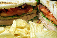 Deli Sandwich. This is an image of a turkey sandwich with chips in the foreground stock image