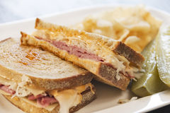Deli style Reuben sandwich with pickles and potato chips Royalty Free Stock Photography