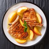 Delicacies: the grilled pork chop is served with glazed peaches royalty free stock photos