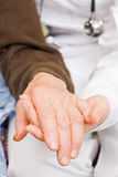 Delicacy. Young doctor holds old man's hand Stock Images