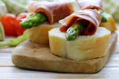 Delicacy appetizer green asparagus and ham stock photos