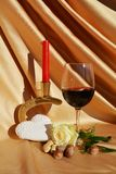 Delicacy and hope. Red wine next to a white ros, a heart and a candle, on an elegant golden background, symbolic image for delicacy and hope in love stock photography