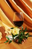 Delicacy. Red wine next to a white rose, on an elegant golden background, symbolic image for delicacy stock photos