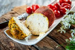 Delicacy round cheese Belper knoll with vegetables and aromatic herbs on a wooden table. Fresh farm products in Russia.  royalty free stock photography