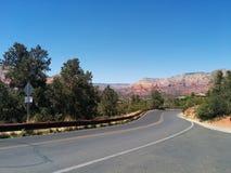 Delicatamente strada di bobina che conduce alle montagne vive fotografia stock