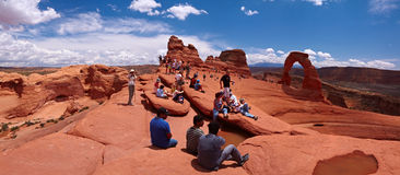Delicate Arch. Tourists, Delicate Arch on background, Arches National Park, Utah, USA Stock Photography