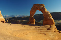 Delicate arch. With tiny person running towards it,  clear sky. Arches National park, Utah USA Stock Photo