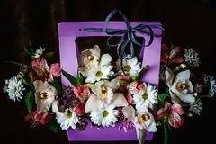 Delicate and beautiful gift bouquet of flowers in a purple cortonal basket. Close-up. Flowers stock photos