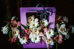 Delicate and beautiful gift bouquet of flowers in a purple cortonal basket. Close-up. Flowers royalty free stock image