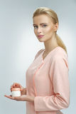 Delicate blond scientist presenting a skin cream Royalty Free Stock Photos