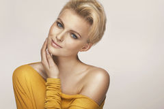 Delicate blonde woman wearing yellow sweater Royalty Free Stock Photos